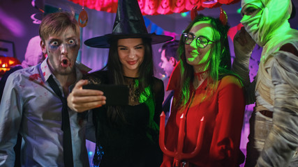 Halloween Costume Party: Brain Dead Zombie, Blood Thirsty Dracula, Bandaged Mummy Beautiful Witch and Seductive She Devil Posing for Group Video Selfie Taken with Smartphone. Monsters Have Fun.
