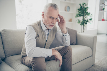 Close up photo amazing he him his aged man silent calm peaceful look wondered think over hand arm temple unsure doubt wear white shirt waistcoat pants sit cozy divan flat house living room indoors