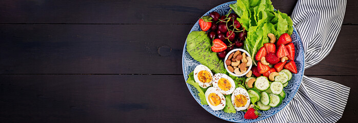 Plate with a paleo diet food. Boiled eggs, avocado, cucumber, nuts, cherry and strawberries. Paleo breakfast. Banner. Top view