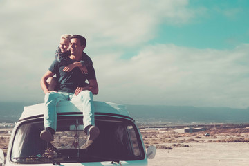 Obraz Travel people concept with young couple of man and woman sitting on the roof of old vintage van - love and relationship for travelers - beautiful landscape background - fototapety do salonu