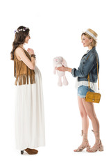 side view of hippie girl giving toy rabbit to pregnant girlfriend isolated on white