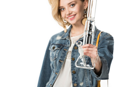 selective focus of stylish hippie girl holding bong isolated on white