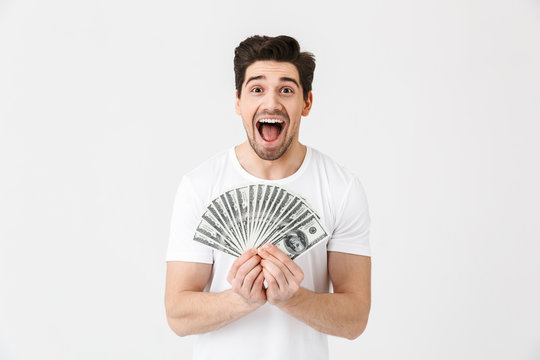 Shocked excited happy young man posing isolated over white wall background holding money.