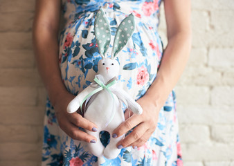 Cropped view of pregnant woman in flowery dress holding cute toy bunny. Future mother in anticipation of baby. Concept of pregnancy and expectation.