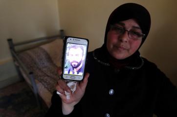 Yusra al-Shomali, 52, shows a picture of her son Alaeddine, 28, who was killed in a battle, in Idlib countryside