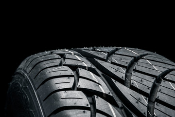Brand new modern car tyre on a black background. Studio shot