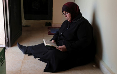 Yusra al-Shomali, 52 reads the Koran inside the apartment that was offered to her in a village built for people who had lost family members during the war, in Idlib countryside