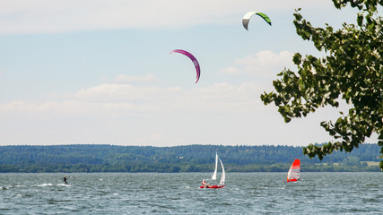 Kitesurfer, windsurfer and small sailboat sailing past each other. A variety of outdoor activities on water concept Wall mural