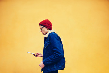 Side view of pensive hipster teen dressed in denim apparel installing application on touch pad walking along promotional background with publicity area.Young man watching videos on websites on tablet