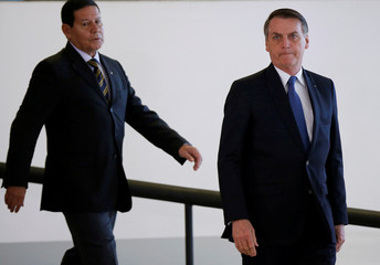 Brazil's President Jair Bolsonaro near the Brazil's Vice President Hamilton Mourao arrive to a ceremony  of the Brazilian National Development Bank (BNDES) Line of Credit for Philanthropic Organizations at the Planalto Palace in Brasilia