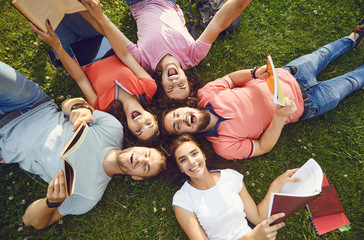 Young people are laughing while lying on the grass