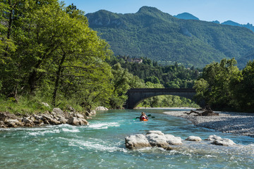 Couple kayaking in a middle on the Drome river with mountains and old stone bridge on the background. Crest area, France.