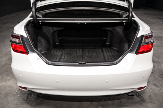 Close up Rear view of a  sedan white car with open trunk in garage. Empty car trunk