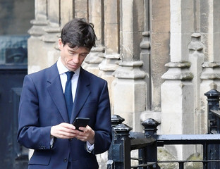 Britain's Secretary of State for International Development Rory Stewart checks his phone outside Houses of Parliament in London