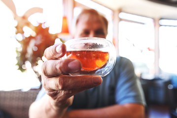 A glass of tea in the hand of a man close-up