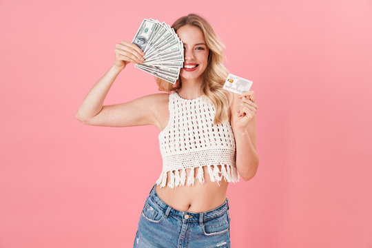 Happy young woman posing isolated over pink wall background holding money and credit card.