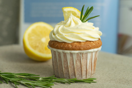 Homemade bakery lemon cupcakes with cheese cream, slice of lemon, branch of rosemary at blue cookbook background at linen tablecloth, selective focus, close up, copy space, from the top.
