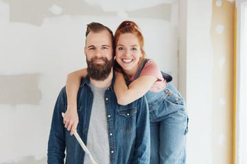 Obraz glückiches paar umarmt sich während der renovierung auf der baustelle - fototapety do salonu