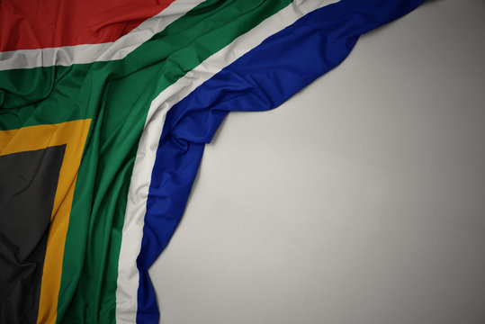 waving national flag of south africa on a gray background.