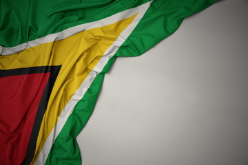 Photo sur Aluminium Amérique du Sud waving national flag of guyana on a gray background.