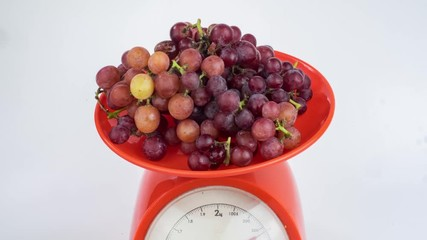 Fototapete - Bunches of grapes in weighing tray of weight scales on white background in Stop Motion