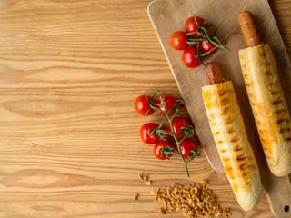 Hot dogi leżące w otoczeniu dodatków na patelni