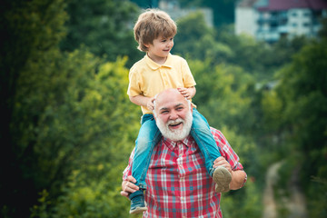 Little boy and grandfather raising hands over sunset sky enjoying life and nature. Portrait of happy grandfather giving grandson piggyback ride on his shoulders and looking up.