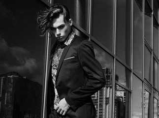 handsome fashion male model dressed in elegant suit posing outdooe. Long haired Metrosexual. Black and white picture.