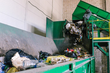 Sort garbage on the plant. Waste at the first stage of processing. The process of separating garbage in a container. Automated line in the emergency room