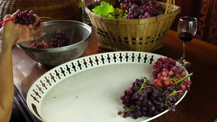 Fototapete - Woman trim a bunch of grapes at a wooden table before packing for sale