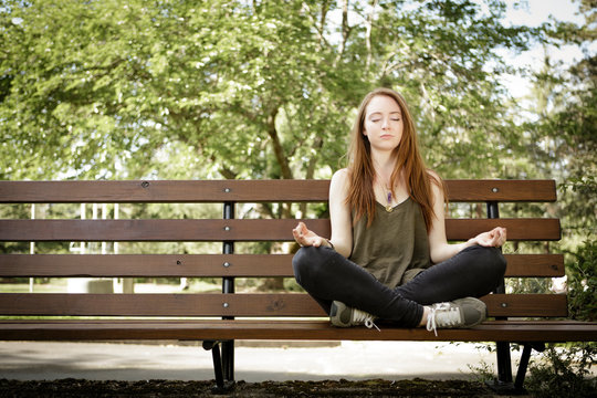 Young woman meditating on park bench