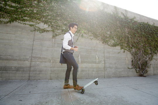 Smiling young man in jeans and vest with skateboard