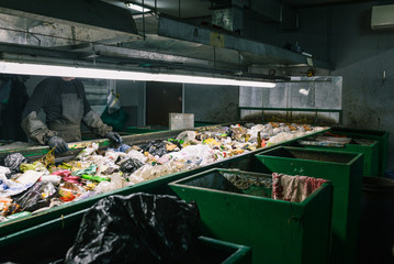 Worker waste sorting plant. Sort garbage. Waste container. Man in gloves and apron