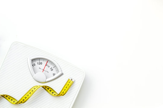 Diet concept with scale and measuring tape for weight loss on white background top view mock up