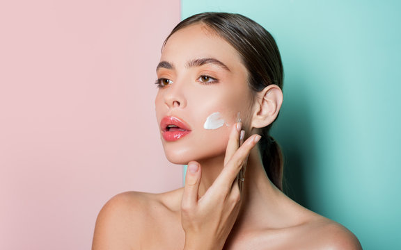 Attractive girl putting anti-aging cream on her face. Closeup Portrait Of Girl With Healthy Smooth Skin.