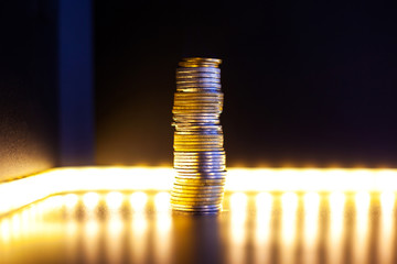 pyramid of silver and gold coins with warm illumination financial pyramid concept