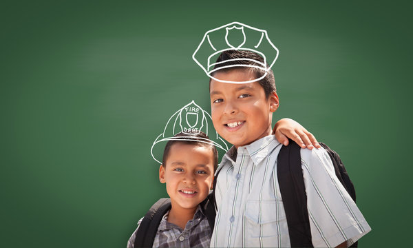 Young Hispanic Student Boy Wearing Backpack Front Of Blackboard with Fireman Helmet And Policeman Hat Drawn In Chalk Over Heads
