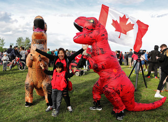Villostas and her son Max react as they watch with a pair of dinosaur mascots in Game 6 of the NBA basketball Finals between the Toronto Raptors and the Golden State Warriors on a large screen in a fan zone in Calgary