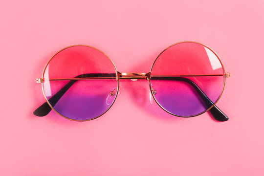 Round summer duotone sunglasses on pink background.