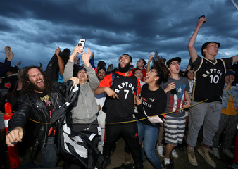 Fans react as the Toronto Raptors defeat the Golden State Warriors in the NBA Finals, while watching on a large screen in a fan zone in Calgary