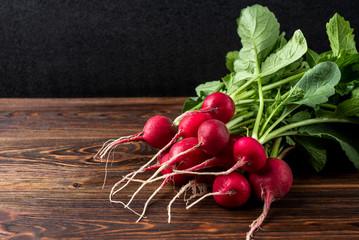 Fototapeta Red radish on dark wooden background. obraz
