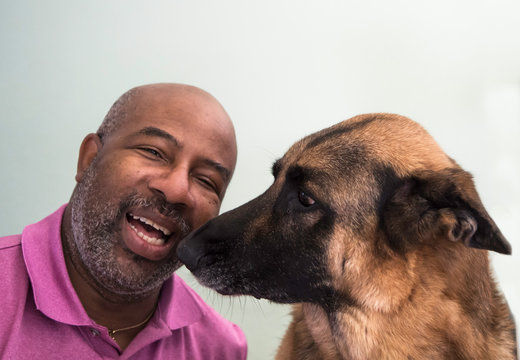 Cute moment between an African American man and his German Shepherd dog who is giving kisses