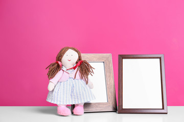 Photo frames and adorable doll on table against color background, space for text. Child room elements