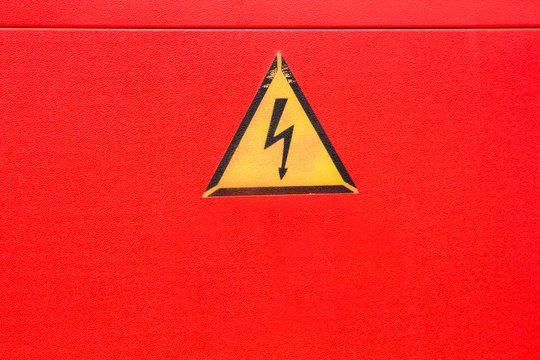 yellow caution high voltage warning sign on bright red background