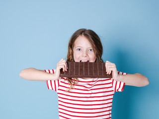 pretty blonde girl with a giant bar of chocolate is posing in front of blue background and is happy smiling