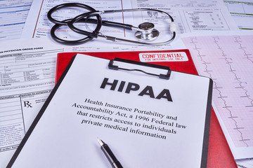 Health Insurance Portability and accountability act HIPAA, red folder with inscription confidential, pen and stethoscope on the medical documents background