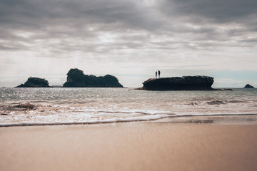 2 people standing on a stone in the water at cathedral cove New Zealand