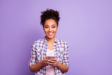 Fototapete - Portrait of satisfied cute pretty youngster hold hand use modern technology get sms messages texting typing chatting communication true user wear checkered shirts isolated on purple background