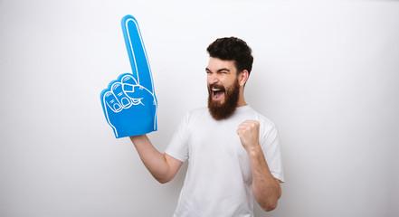 Winner bearded man with a blue foam finger screaming loadly of happines.