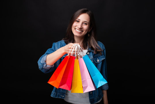 Beautiful young woman smiling at the camera showing her colorful shopping paper bags on black background.